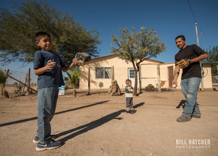 Photo by Bill Hatcher (Instagram: @bhatcherphoto). A father plays catch with his two children.