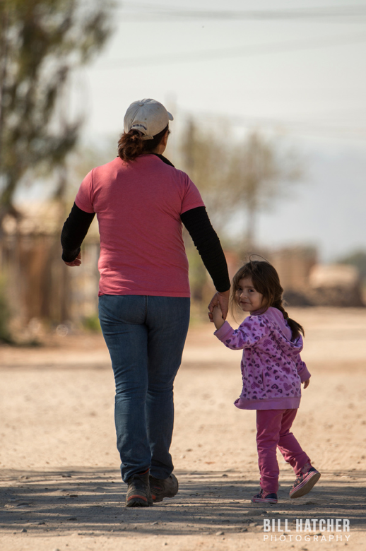 Photo by Bill Hatcher (Instagram: @bhatcherphoto). mother and her daughter take a walk in their hometown near the border.